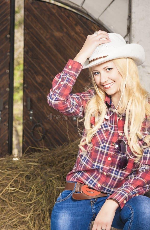 Αισθησιακό ξανθό Cowgirl που χαμογελά μέσα του αγροτικού σπιτιού κάθετος στοκ εικόνα με δικαίωμα ελεύθερης χρήσης