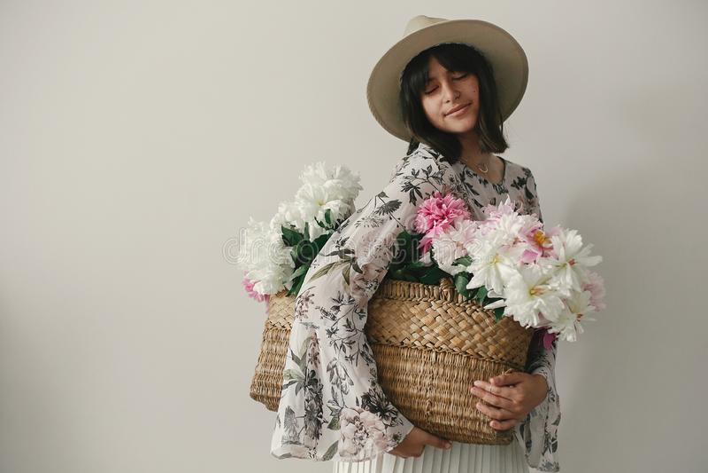 Αισθησιακό πορτρέτο του κοριτσιού boho που κρατά τα ρόδινα και άσπρα peonies στο αγροτικό καλάθι Μοντέρνη γυναίκα hipster στο καπ στοκ φωτογραφία