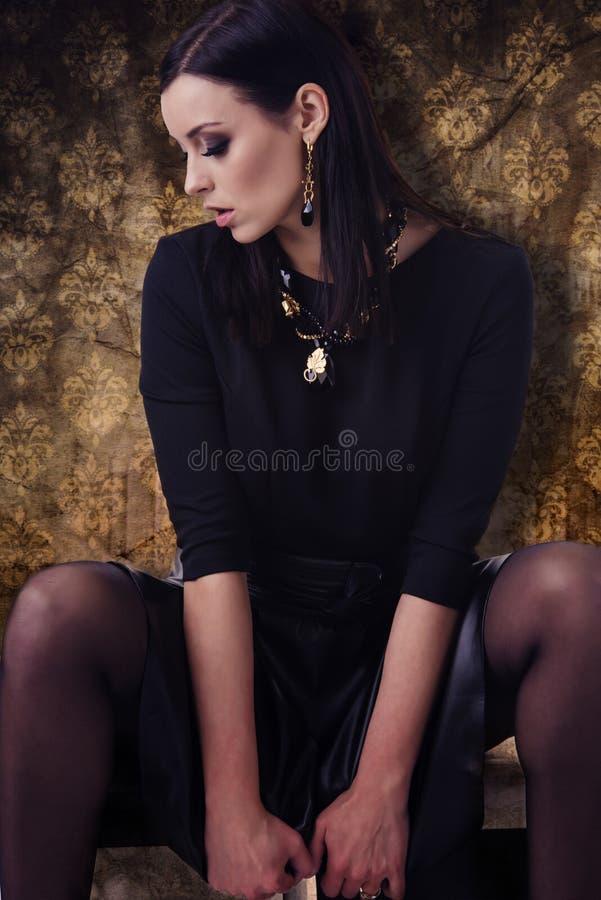 Αισθησιακό πρότυπο μόδας στα μαύρα ενδύματα με τα κοσμήματα πέρα από το χρυσό υπόβαθρο σχεδίων στοκ εικόνες