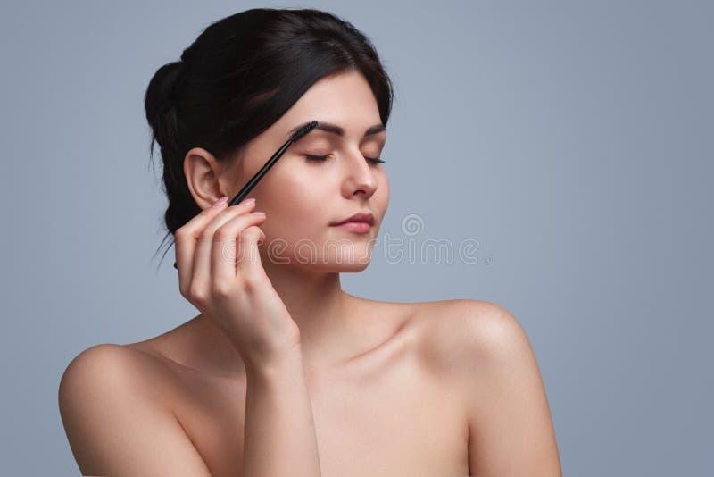 Αισθησιακό brunette που ισχύει makeup στοκ εικόνες με δικαίωμα ελεύθερης χρήσης
