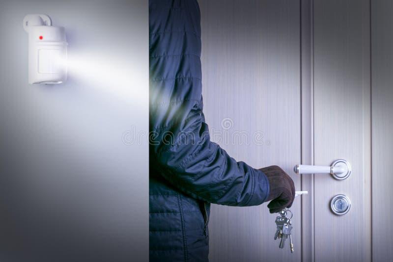 Αισθητήρας ή ανιχνευτής κινήσεων για το σύστημα ασφαλείας επικίνδυνος διαρρήκτης με το σπάσιμο στην εγχώρια πόρτα ενός θύματος στοκ εικόνες με δικαίωμα ελεύθερης χρήσης