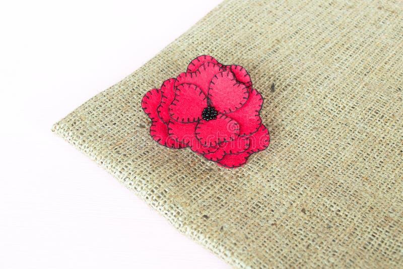 Αισθητό κόκκινο λουλούδι burlap και το άσπρο ξύλινο υπόβαθρο στοκ φωτογραφία