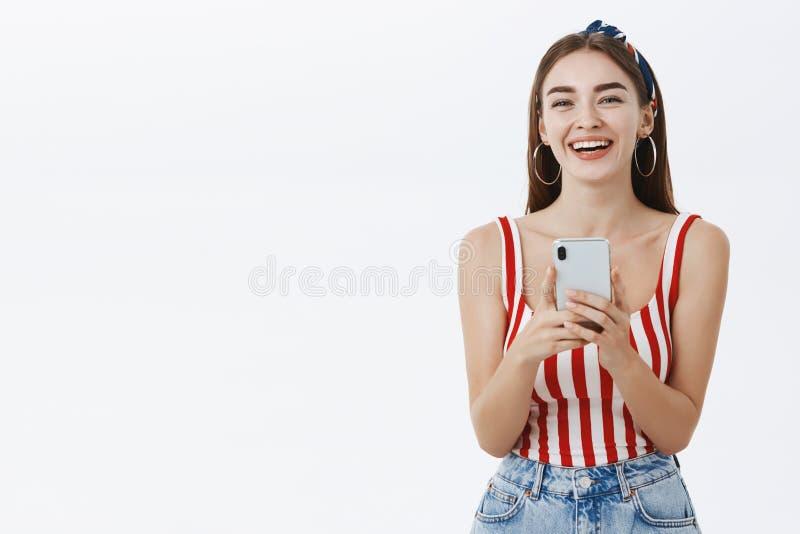 Αισιόδοξη ευτυχής νέα γυναίκα στη ριγωτή κορυφή pinup και headband το γέρνοντας κεφάλι που γελά από διασκέδασης και χαράς με στοκ φωτογραφία