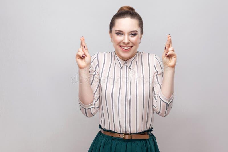 Αισιόδοξη όμορφη νέα γυναίκα στο ριγωτό πουκάμισο και makeup και την απαγόρευση hairstyle, στεμένος με τα διασχισμένα δάχτυλα και στοκ φωτογραφία