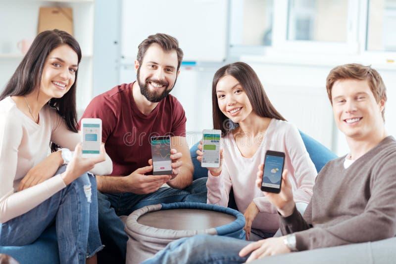 Αισιόδοξοι τέσσερις φίλοι που παρουσιάζουν συσκευές τους στοκ φωτογραφίες