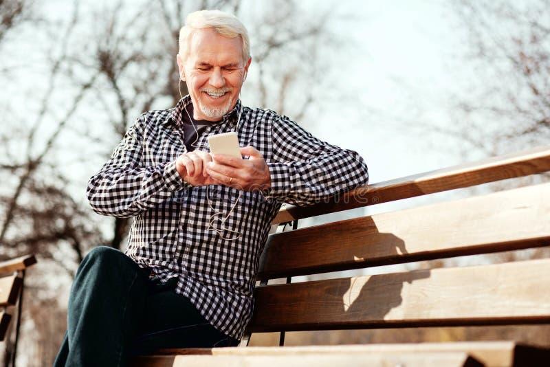 Αισιόδοξο ανώτερο άτομο που αποφασίζει για το playlist στοκ φωτογραφία με δικαίωμα ελεύθερης χρήσης