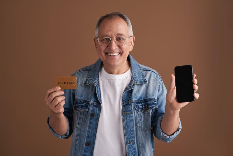 Αισιόδοξο μΑ που απολαμβάνει να πληρώσει on-line με το smartphone του στοκ φωτογραφίες