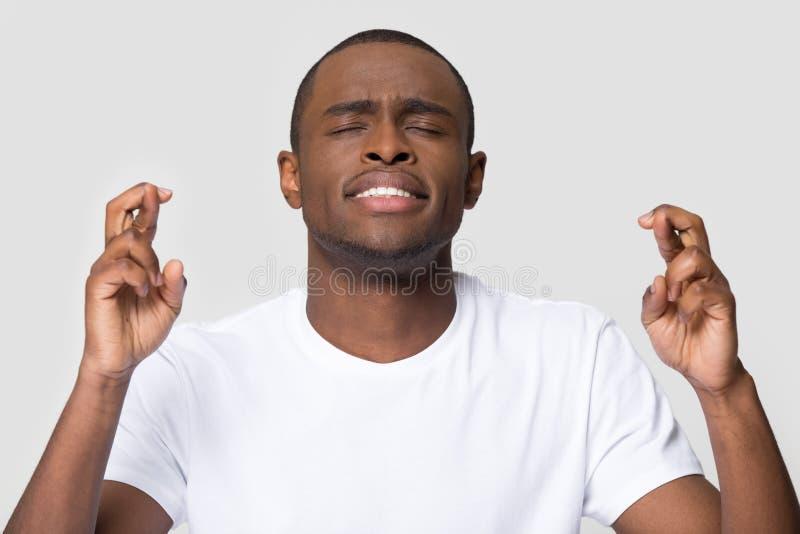 Αισιόδοξο νέο αφρικανικό άτομο που διασχίζει τα δάχτυλα που επιθυμούν για την καλή τύχη στοκ εικόνα