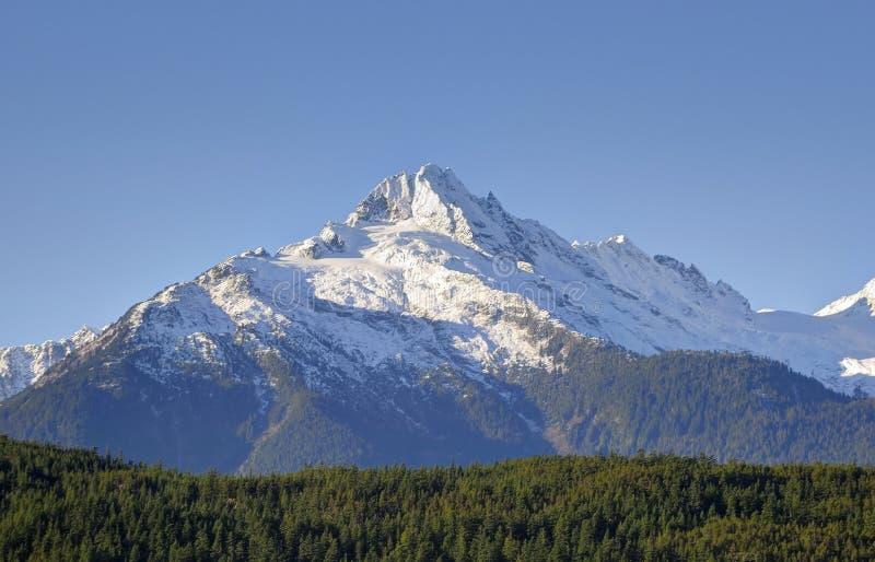 Αιχμές της σειράς Tantalus στο νότιο τέλος των παράκτιων βουνών της Βρετανικής Κολομβίας, Καναδάς ενάντια στο μπλε ουρανό στοκ φωτογραφία