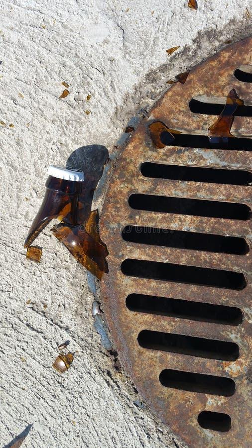 Αιχμηρό σπασμένο γυαλί μπουκαλιών από το σκουριασμένο αγωγό θύελλας στο χώρο στάθμευσης στοκ εικόνες με δικαίωμα ελεύθερης χρήσης
