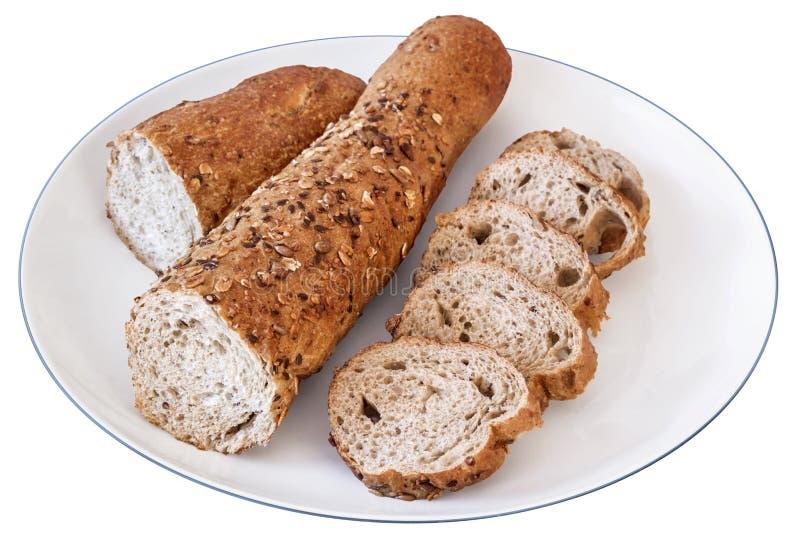 Ακέραιο καφετί ψωμί Baguette που κόβεται στις φέτες στο άσπρο πιάτο Isola στοκ εικόνα