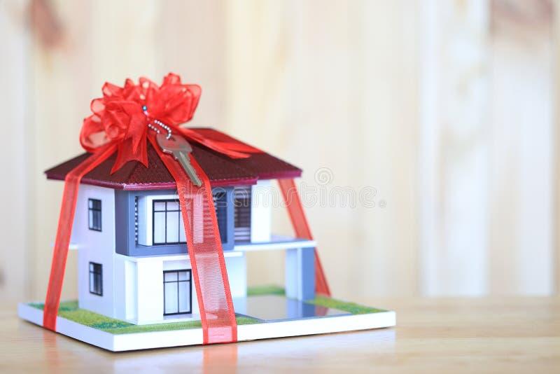 Ακίνητη περιουσία και νέα εγχώρια έννοια δώρων, πρότυπο σπίτι με την κόκκινη κορδέλλα και κλειδί στο άσπρο υπόβαθρο στοκ φωτογραφίες