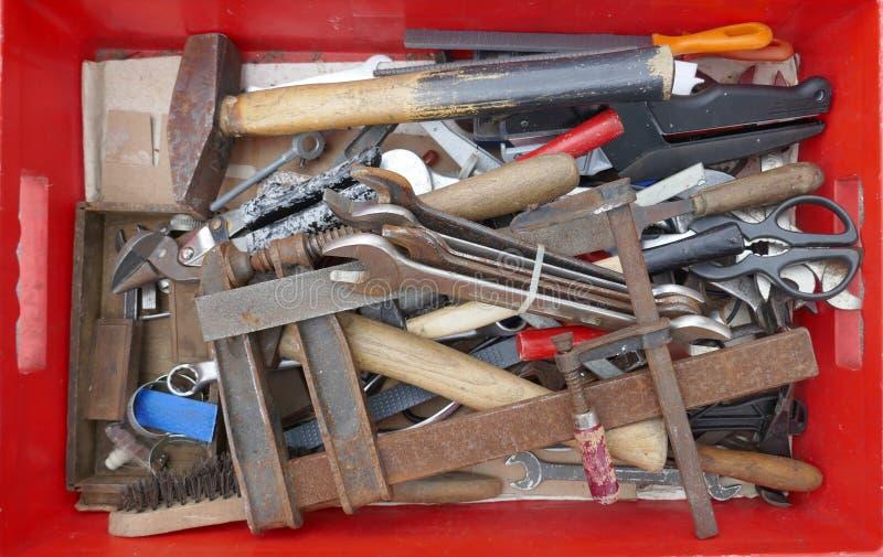 Ακατάστατα παλαιά σκουριασμένα εργαλεία χεριών σε ένα κόκκινο πλαστικό κιβώτιο στοκ φωτογραφίες