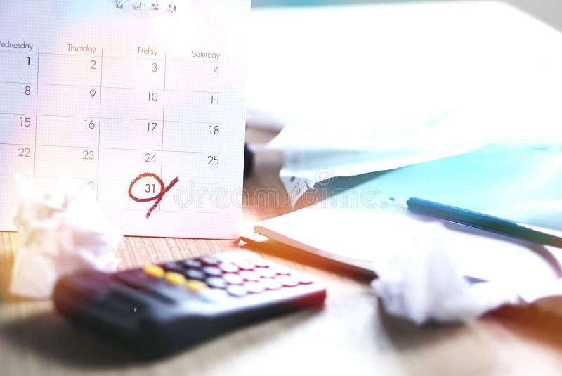 Ακατάστατο γραφείο γραφείων κατά τη διάρκεια της φορολογικής εποχής με την προθεσμία σε ένα ημερολόγιο στοκ εικόνα με δικαίωμα ελεύθερης χρήσης