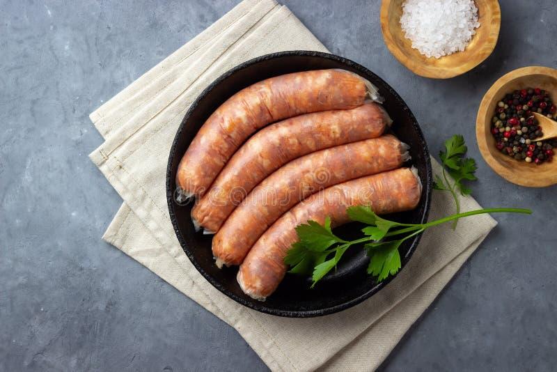 Ακατέργαστα άψητα λουκάνικα κρέατος και πράσινα χορτάρια στοκ φωτογραφίες