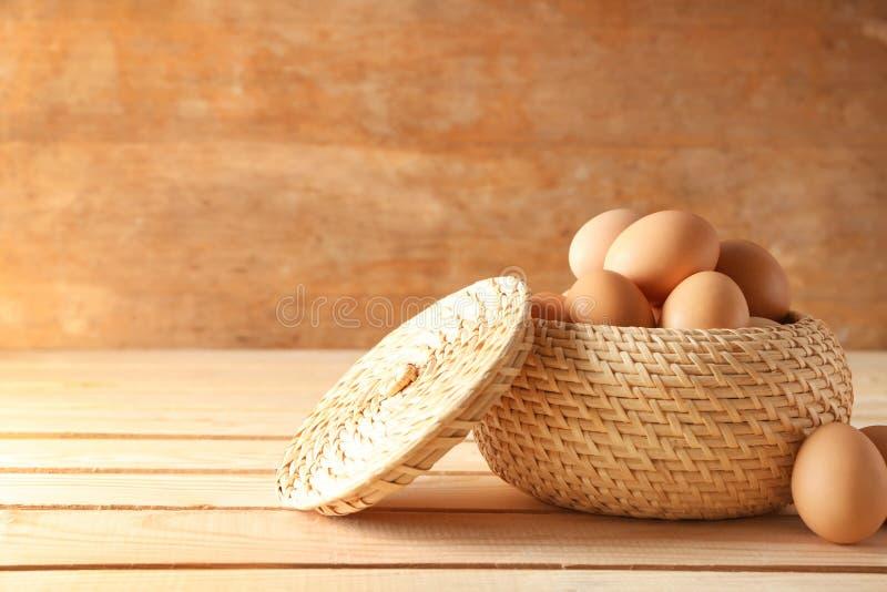 Ακατέργαστα αυγά κοτόπουλου στο ψάθινο κύπελλο στον ξύλινο πίνακα στοκ εικόνες με δικαίωμα ελεύθερης χρήσης