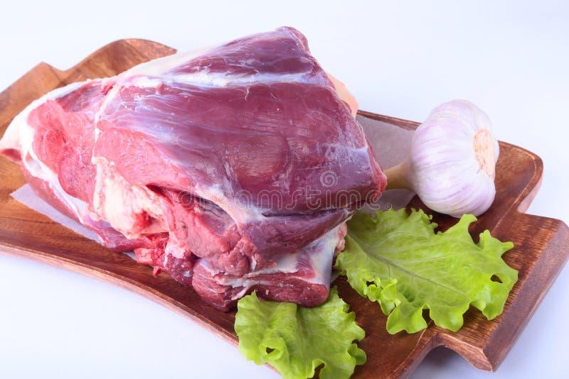 Ακατέργαστα κνήμες βόειου κρέατος, σκόρδο και φύλλο μαρουλιού στο ξύλινο γραφείο που απομονώνεται στο άσπρο υπόβαθρο άνωθεν και τ στοκ φωτογραφίες