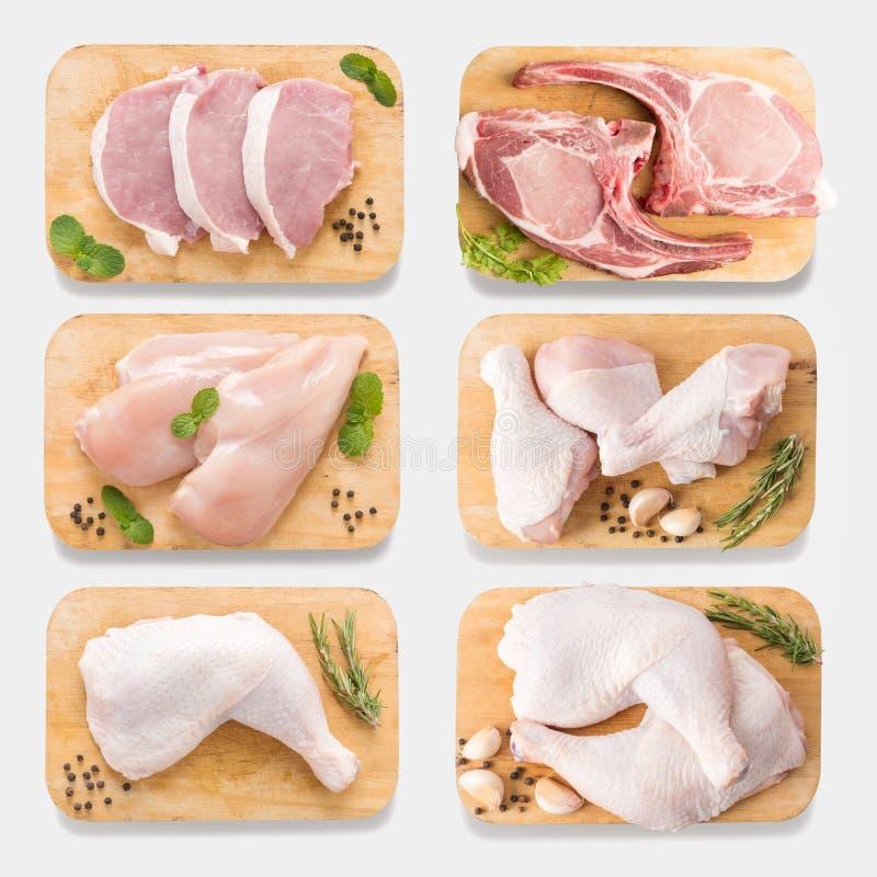 Ακατέργαστα κοτόπουλο και χοιρινό κρέας προτύπων στον τέμνοντα πίνακα που τίθεται απομονωμένος επάνω στοκ εικόνες