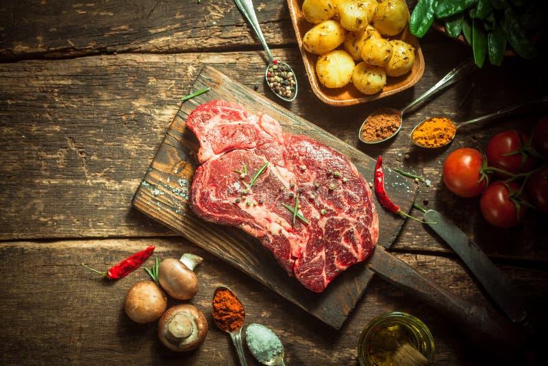 Ακατέργαστα κρέας χοιρινού κρέατος, χορτάρια, καρυκεύματα και Veggies στον πίνακα στοκ φωτογραφίες