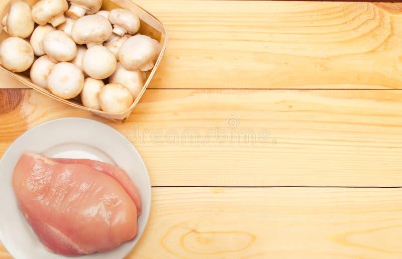 Ακατέργαστα λωρίδα και μανιτάρια κοτόπουλου σε ένα ξύλινο υπόβαθρο Θέση φ στοκ φωτογραφία