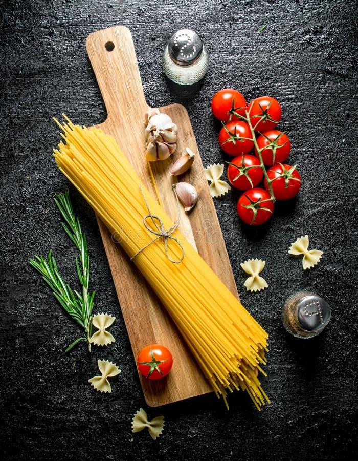 Ακατέργαστα μακαρόνια σε έναν ξύλινο τέμνοντα πίνακα με το σκόρδο, τις ντομάτες και το δεντρολίβανο στοκ φωτογραφία με δικαίωμα ελεύθερης χρήσης