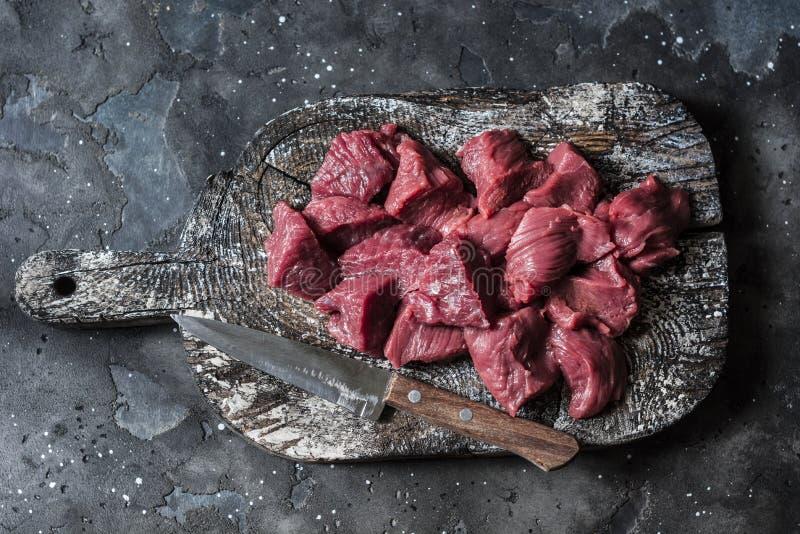 Ακατέργαστα οργανικά κομμάτια κρέατος λωρίδων βόειου κρέατος στον ξύλινο αγροτικό τέμνοντα πίνακα στο σκοτεινό υπόβαθρο, τοπ άποψ στοκ εικόνες