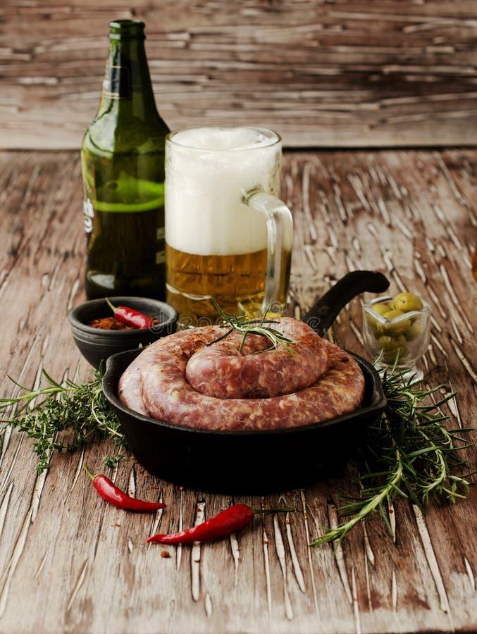 Ακατέργαστα λουκάνικα βόειου κρέατος σε μια παν, εκλεκτική εστίαση χυτοσιδήρων στοκ εικόνα