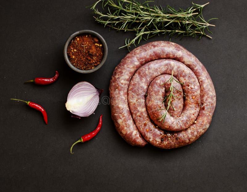 Ακατέργαστα λουκάνικα βόειου κρέατος σε μια παν, εκλεκτική εστίαση χυτοσιδήρων στοκ φωτογραφία