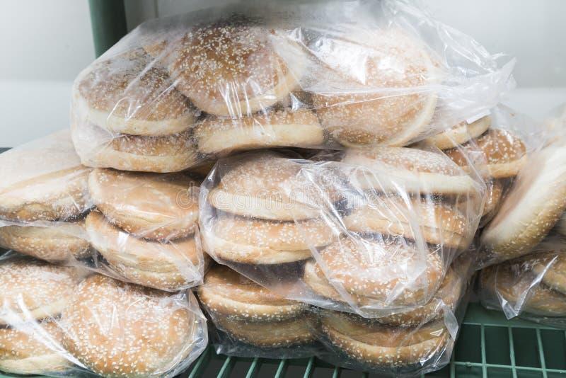 Ακατέργαστα παγωμένα κουλούρια για τα burgers της άσπρης ζύμης που συσκευάζεται στις διαφανείς πλαστικές τσάντες στοκ φωτογραφία με δικαίωμα ελεύθερης χρήσης