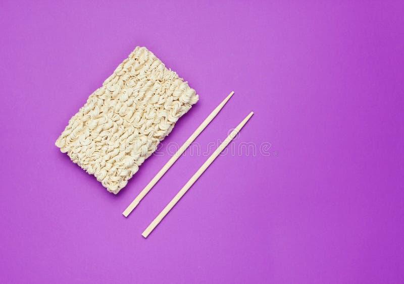 Ακατέργαστα στιγμιαία νουντλς και κινεζικά chopsticks στοκ εικόνα