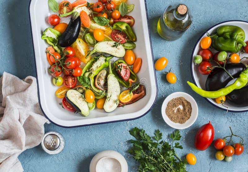 Ακατέργαστα συστατικά για το μεσημεριανό γεύμα - φρέσκα τεμαχισμένα λαχανικά στο τηγάνι σε ένα μπλε υπόβαθρο, τοπ άποψη στοκ εικόνες