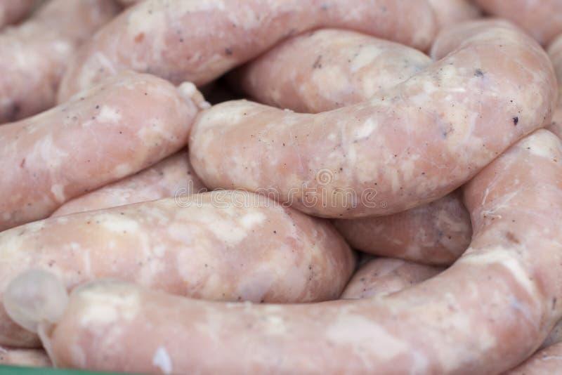 Ακατέργαστα φρέσκα λουκάνικα χοιρινού κρέατος για το ψήσιμο στη σχάρα Εκλεκτική εστίαση στοκ φωτογραφία με δικαίωμα ελεύθερης χρήσης