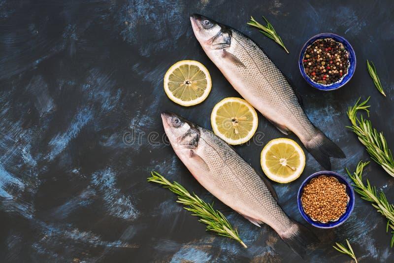 Ακατέργαστα ψάρια με τα καρυκεύματα και ασβέστης σε ένα μπλε υπόβαθρο Πέρκες θάλασσας σε ένα μπλε αφηρημένο υπόβαθρο, τοπ άποψη,  στοκ φωτογραφία
