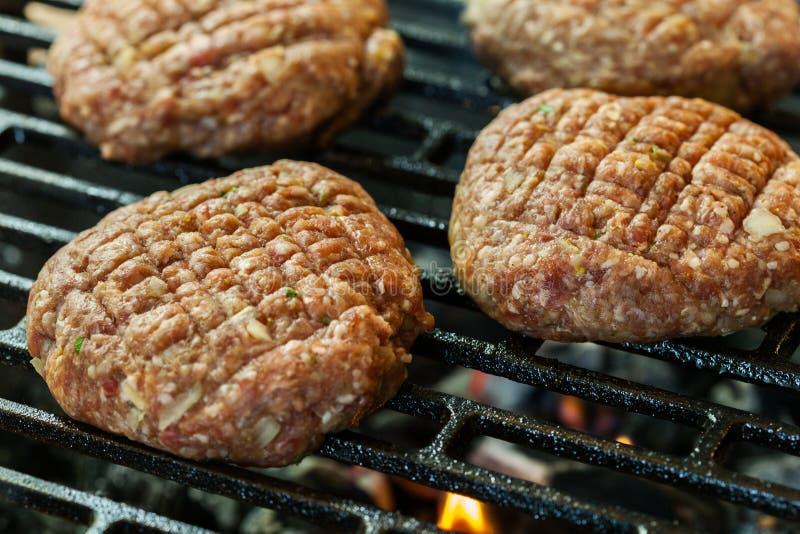 Ακατέργαστα burgers στη σχάρα σχαρών με την πυρκαγιά στοκ φωτογραφίες