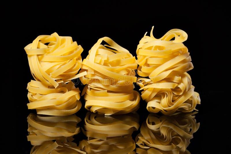 Ακατέργαστες άψητες φωλιές tagliatelle στο μαύρο υπόβαθρο με την αντανάκλαση ιταλικά ζυμαρικά παραδο&sig στοκ φωτογραφία με δικαίωμα ελεύθερης χρήσης