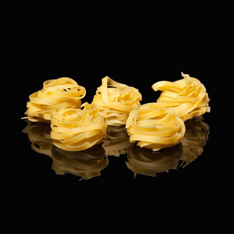 Ακατέργαστες άψητες φωλιές tagliatelle στο μαύρο υπόβαθρο με την αντανάκλαση ιταλικά ζυμαρικά παραδο&sig στοκ εικόνα