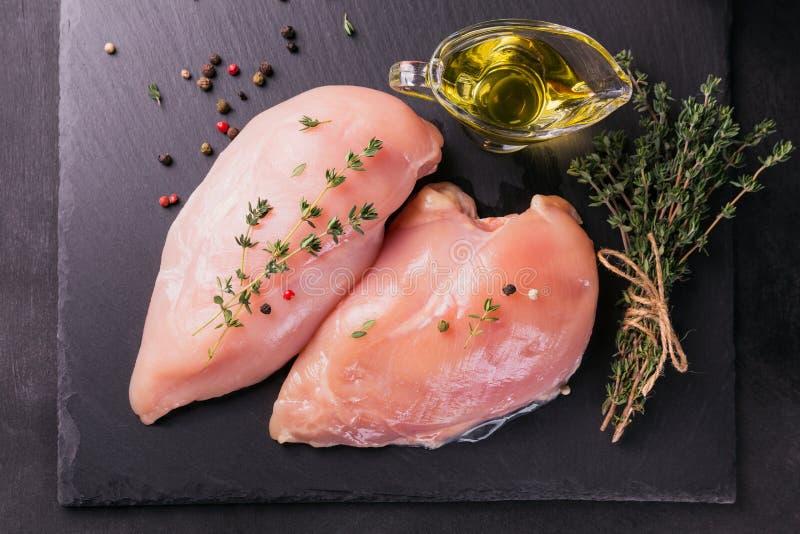 Ακατέργαστες λωρίδες κοτόπουλου με τα καρυκεύματα και τα χορτάρια στοκ φωτογραφίες