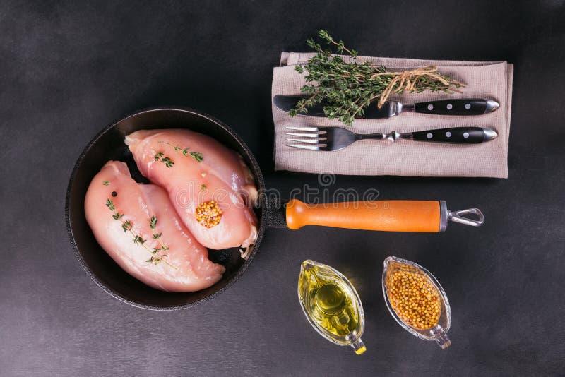 Ακατέργαστες λωρίδες κοτόπουλου με τα καρυκεύματα και τα χορτάρια στοκ εικόνες