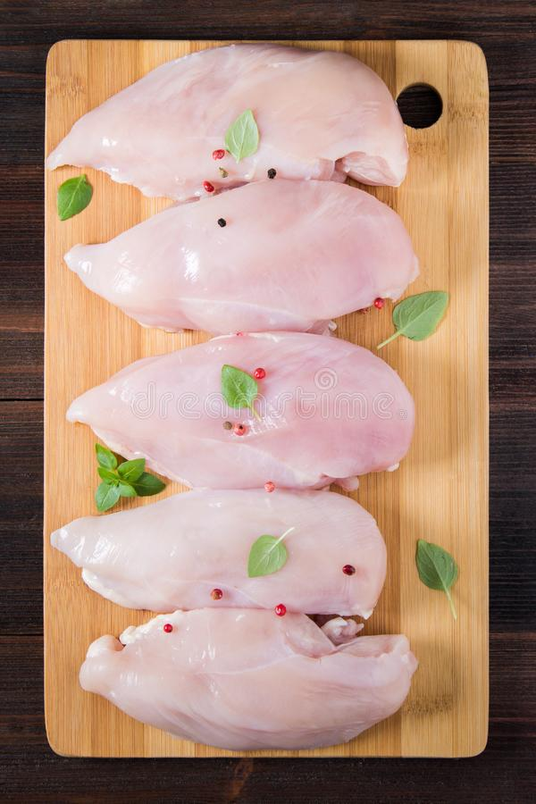 Ακατέργαστες λωρίδες κοτόπουλου σε έναν πίνακα κοπής στα πλαίσια ενός ξύλινου πίνακα Συστατικά κρέατος για το μαγείρεμα Κενή θέση στοκ φωτογραφία με δικαίωμα ελεύθερης χρήσης