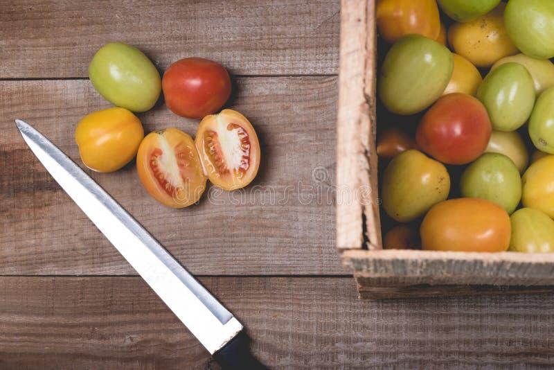 Ακατέργαστες ντομάτες σε ένα ξύλινο υπόβαθρο στοκ εικόνες