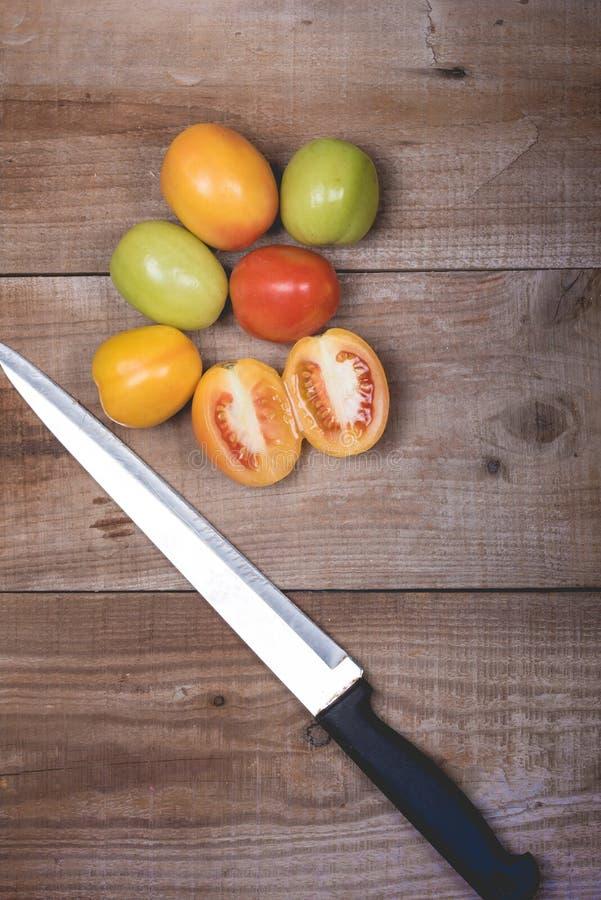 Ακατέργαστες ντομάτες σε ένα ξύλινο υπόβαθρο στοκ φωτογραφία