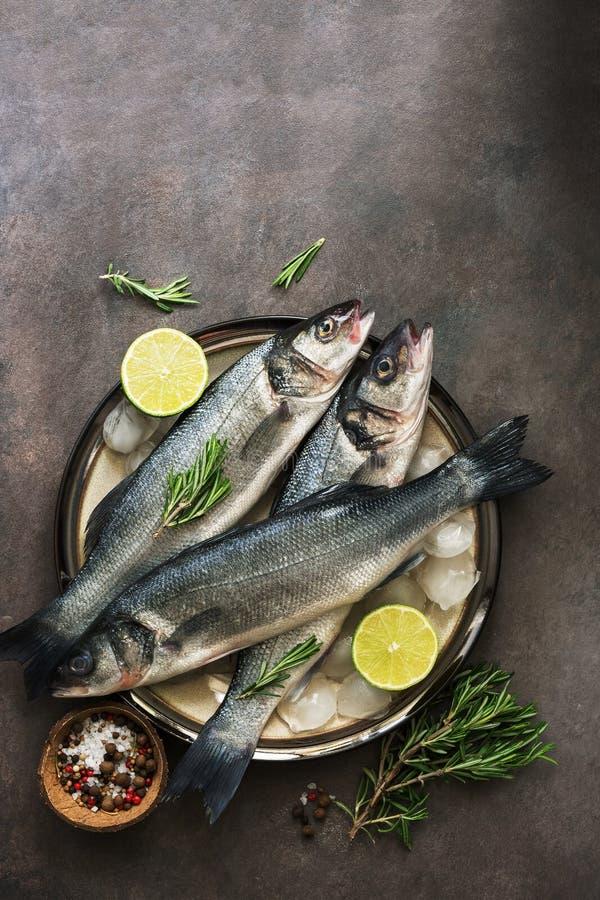 Ακατέργαστες πέρκες θάλασσας ψαριών θάλασσας σε ένα πιάτο με τον πάγο, το δεντρολίβανο και το λεμόνι, σκοτεινό καφετί αγροτικό υπ στοκ φωτογραφία με δικαίωμα ελεύθερης χρήσης