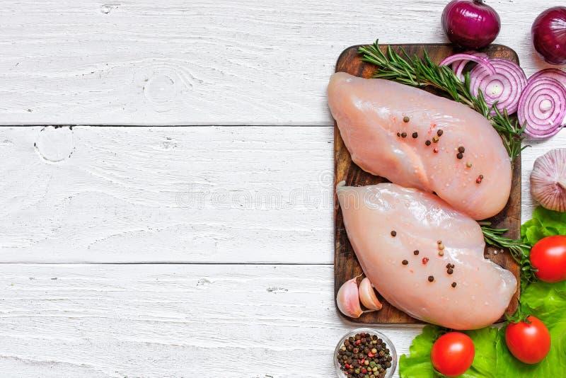 Ακατέργαστες λωρίδες στηθών κοτόπουλου στον ξύλινο τέμνοντα πίνακα με τα λαχανικά και τα καρυκεύματα στοκ φωτογραφία