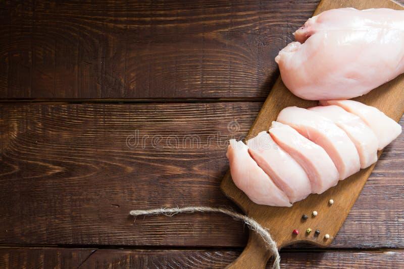 Ακατέργαστες λωρίδες στηθών κοτόπουλου στον ξύλινο τέμνοντα πίνακα στοκ φωτογραφία με δικαίωμα ελεύθερης χρήσης