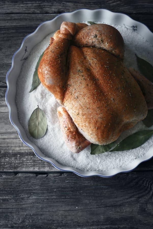 Ακατέργαστη ημέρα των ευχαριστιών Τουρκία με τα καρυκεύματα στο πιάτο ψησίματος με την κατακόρυφο φύλλων άλατος και κόλπων στοκ εικόνες