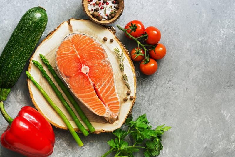Ακατέργαστη μπριζόλα σολομών στο κολόβωμα με τα φρέσκα λαχανικά, γκρίζο υπόβαθρο Κολοκύνθη, γλυκά πιπέρια, σπαράγγι, ντομάτα και  στοκ φωτογραφία