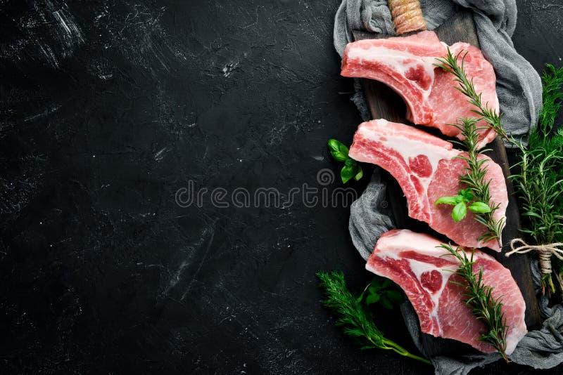 Ακατέργαστη μπριζόλα στο κόκκαλο Κρέας με τα καρυκεύματα και τα χορτάρια Σε ένα μαύρο υπόβαθρο πετρών στοκ εικόνες