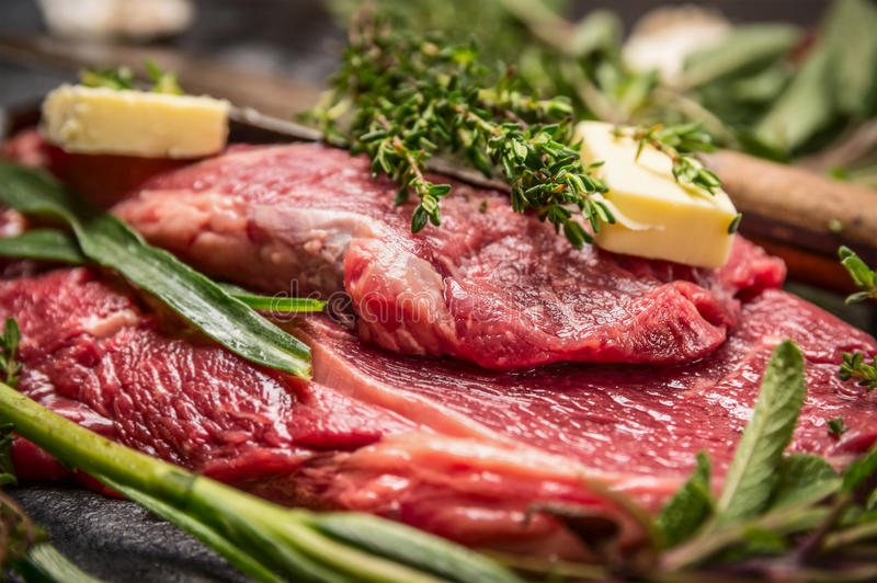 Ακατέργαστη μπριζόλα βόειου κρέατος με τα χορτάρια και βούτυρο για τη σχάρα ή το μαγείρεμα στοκ εικόνες με δικαίωμα ελεύθερης χρήσης
