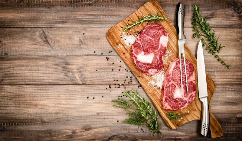 Ακατέργαστη μπριζόλα Ribeye κρέατος με τα χορτάρια και τα καρυκεύματα κόκκινος τρύγος ύφους κρίνων απεικόνισης στοκ φωτογραφία με δικαίωμα ελεύθερης χρήσης