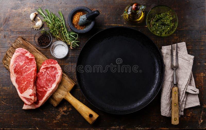 Ακατέργαστη μπριζόλα Striploin κρέατος με τα συστατικά γύρω από το τηγάνι στοκ εικόνες